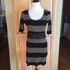 """NWOT black and gray wide stripe dress. Wide black and gray stripe dress. Very cute belted as shown (belt does not come with outfit). Stretchy comfortable fabric. 80% cotton 40% modal. Size tagged as large but is cut small so would be perfect for someone that is a small or medium. Can also be worn as cute long top over skirt or pants. Length from shoulder seam to bottom is 33"""". New/never worn!! Express Dresses"""