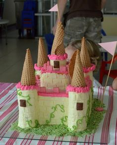 File it away for the next princess party.  Castle cake pan, iced, plus ice cream cone turrets.  Via Crafterhours.