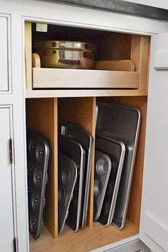 Use cabinet dividers to keep muffin tins and cookie sheets in order. A full-extension shelf above means no more kneeling and rooting around in a dark base cabinet for the right pot lid.