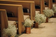 DIY baby's breath arrangements as aisle decorations for a rustic wedding ceremony.