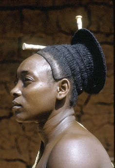 "Africa | Mbombio, Chief Mogendo's principal wife, Medje village, DR Congo |  ©Eliot Elisofon. 1970 |  ""The funnel-shaped coiffure which ended in an outward halo, originally symbolic of high social status, was considered exceptionally attractive, and took a lot of time to create. Of the ornaments that embellished the hairstyles of the Mangbetu, and related ethnic groups, combs were reserved for women."" [Sieber R., Herreman F., 2000: Hair in African Art and Culture, Prestel]."