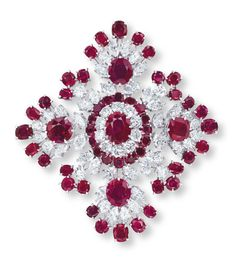 A RUBY AND DIAMOND BROOCH, BY VAN CLEEF & ARPELS  The openwork lozenge shape panel of foliate design, centering upon an oval-shaped ruby, within a brilliant-cut diamond and circular-cut ruby two-tiered surround and marquise-cut diamond trim, extending to the oval-shaped ruby and marquise-cut diamond quatrefoil clusters, alternating with old European-cut diamond and circular-cut ruby accents, mounted in 18k white gold, 5.8 cm long, with French assay mark for gold
