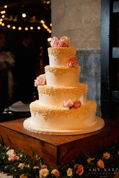 White brides cake with pink flowers on wooden crate - Photo by Amy Karp Photography