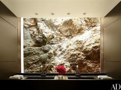 A guest bathroom window frames a craggy expanse of the cliffside | archdigest.com