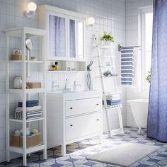 Salle de bains blanche avec meuble lavabo, étagère et élément à miroir HEMNES en blanc, rideau de douche bleu et serviettes bleues et blanches.