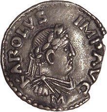 Denier impérial en argent de Charlemagne, inspiré des modèles romains. Au droit, le profil moustachu, le front ceint de lauriers, et l'inscription «KAROLUS IMP[ERATOR] AUG[USTUS]» (Charles, empereur auguste)[1] (Cabinet des Médailles, Paris).