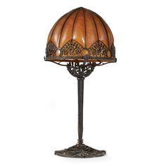 RAYMOND SUBES (1891 - 1970) A TABLE LAMP wrought iron and moulded glass, the domed mottled orange/red shade above a tapering stem and circular base, mounted with stylised foliage 70cm. high by 35.5cm. diam.; 2ft 3½in., 1ft 2in. circa 1930