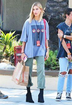 Hailey Baldwin apostou em uma t-shirt oversized com calça verde e botas pretas.