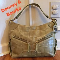 "DOONEY & BOURKE Leather Hobo Purse This is a simply Gorgeous bag!!!  Excellent Condition!!!  A beautiful Sage green great for Spring and Fall. Magnetic snap closure, 2 front zip pockets for extra storage, side accent buckles, gold tone hardware. Interior has zip pocket, slip pocket and key hook.  Metal D & B hang tag. Shoulder strap with 10"" drop, measures 15""x10""x7"". Dooney & Bourke Bags Hobos"