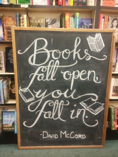 """Books fall open, you fall in"" chalkboard art for a bookstore window display."