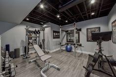 Design meets wellness! Recreate this look with DURA WOOD (Galveston Gray) #gymdesign #gymmotivation #homegym #durableflooring #homegymsetup #workoutathome #luxuryhomes #luxuryhomegym #stayhomestaysafe #exerciseathome #sweatathome #fitnessmotivation Home Gym Basement, Gym Room At Home, Rustic Basement, Modern Basement, Basement Bedrooms, Basement Ideas, Basement Layout, Basement Makeover, Basement Designs