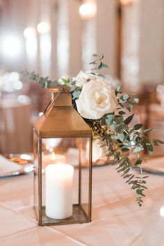 Courtney Inghram Events floral design photographed by Audrey Rose Photography at Early Mountain Vineyards in Virginia. Organic wedding centerpiece with gold lantern, white flowers with eucalyptus. Wedding flowers with gold lanterns and eucalyptus greenery and white flowers. Winter vineyard wedding. Centerpiece for winery wedding with garden-inspired natural textures and white pillar candles