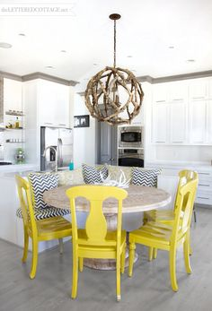 Creative kitchen space. Great counter with built-in bench. Also love the brightly painted chairs.