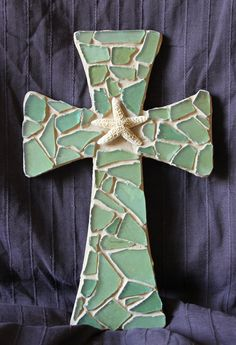 This beach themed mosaic cross is a beautiful addition to any room. It measures 11x7 and the base is made of birch wood. The mosaic is sea green broken glass and the grout is sand color. The Starfish is from the Texas coast. There is a wall hanging hook on the back for easy wall mounting.