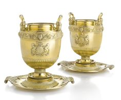 Property from the Collections of Lily & Edmond J. Safra - A pair of George III silver-gilt wine coolers & stands, Benjamin Smith, retailed by Rundell, Bridge & Rundell, London, 1807, the circular dished stands with ovolo borders & acanthus scroll handles, the vase-shaped bodies partly gadrooned below applied arms, collar of scrolling grapevine on matted ground with masks of Bacchus & Ceres, the hoop handles rising from Greek heads, detachable gadrooned rims... height overall 13 in.