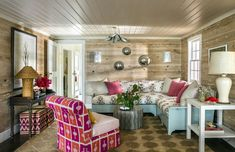 A pattern-punched great room is balanced with wood paneled walls and a rattan lamp.