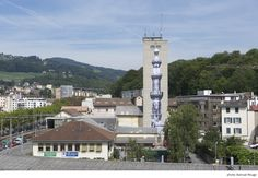 """After the construction of new minarets was outlawed in Switzerland, French street artist pasted a 40-meter-high photograph of a minaret on an old grain elevator in Vevey, on the Swiss Riviera, during the 2010 Images Festival . The installation is called """"Unframed."""" The silo minaret photo is by Lehnert & Landrock, noted Swiss photographers from the early part of the 20th C. (Photo by Samuel Rouge)."""