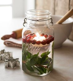 Place a branch of greenery at the bottom of a glass jar or vase. Fill the jar about two-thirds full with water. Drop in cranberries and a floating candle. Its soft, flickering flame will add ambience to your dinner-party table.