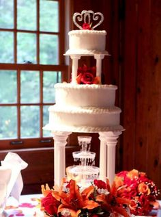 Multiple tier wedding cake with Roman columns and fontain with crystal topper and red roses.JPG