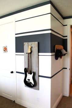 """For the guitar """"art"""" I just picked up some fence planks at Home Depot for about $5, and screwed them together using the plank scraps on the..."""