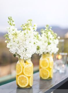 Easy summer centerpiece:  Add fresh lemons to Mason jars and fill with fresh flowers.