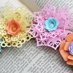 If you follow the links, you'll end up at the Fiskars site (won't let me pin) which shows you how to make these pretty flowers with corner punches.