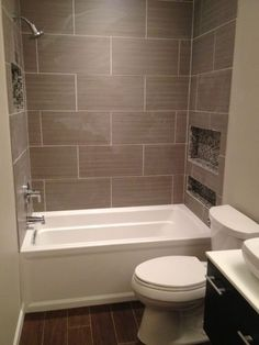 Pic only.  Large surround tile example, vanity with vessel sink, wood look? vinyl tile?