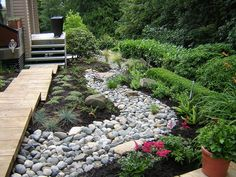 "If you want to make a dramatic statement in your garden, without a lot of maintenance, a DIY dry creek bed is the way to go. Try these DIY dry creek landscaping ideas to give your yard that ""wow"" factor without the upkeep of a true water feature! River Rock Landscaping, Landscaping On A Hill, Landscaping With Rocks, Landscaping Ideas, Southern Landscaping, Residential Landscaping, Natural Landscaping, Stone Landscaping, Walkway Ideas"