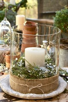 Great centerpiece! Fill a vase with greenery and a candle, sprinkle the greenery with fake snow, tie a burlap scrap around it with some twine