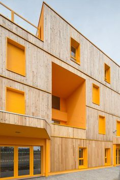 Doors, windows and recesses are picked out in yellow ochre on the timber facade of this retirement home near Paris.