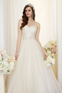 This gorgeous #gown features a figure-flattering asymetrical bodice that gathers at the natural waist under a diamante floral beading motif. The skirt flows full into an elegant cathedral train. @essensedesigns