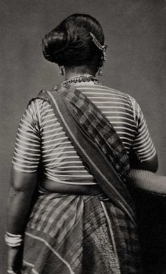 Portrait of a lady's back, c. 1870. Gauging from her garments, she appears south Indian, wearing the chequered pattern of textile from Tamil Nadu for a sari and a striped silk blouse. The photograph allows for the silver ornaments in her hair and neck to be seen from behind.