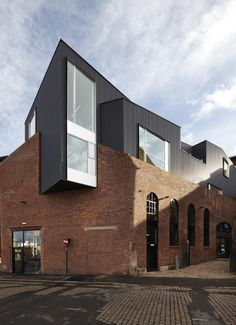 The two storeys that London architects Project Orange have added to the roof of a redundant brick warehouse in Sheffield look like another building stacked on top.  A new restaurant and bar occupies the double-height warehouse space below, where it benefits from light through the original two-storey-high arched windows.
