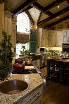 """Una colección de animales salvajes de detalle se metió en esta acogedora cocina, incluyendo el techo de madera expuesta viga, encimeras de mármol beige, pisos de madera, isla madera negro, y """"edad"""" gabinetes de madera pintado de la luz, acentuado por persianas verdes brillantes."""
