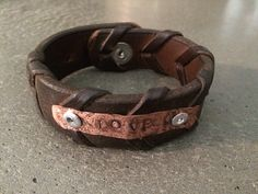 This is our first try at a bracelet. The leather is from a Horse bridle, and the copper is hammered from solid round stock and etched for texture. Pop rivets holds it in place.