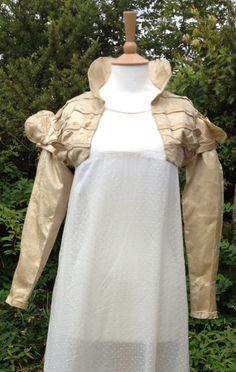 1821 cream/gold silk spencer. Puffed oversleeves. Piped edging. Hussar style decoration on bodice with piped-edge petals. Worn by Mary Ellis Cole at her wedding to Captain James Agnew Stevens in Cornwall 1821. Books of the whole Sylvestra Regency Fashion collection available! http://www.blurb.co.uk/search/site_search?search=sylvestra+regency