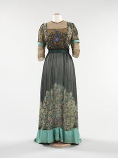 evening gown, circa 1910 uses printed silk, along with embroidery, to produce its design. Peacocks were an incredibly popular motif in the Edwardian era.