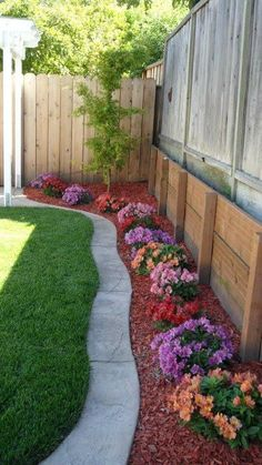 [i like the red mulch. The small flower bushes. But I'd like them all the same color or two alternating colors. On the driveway side of the house]