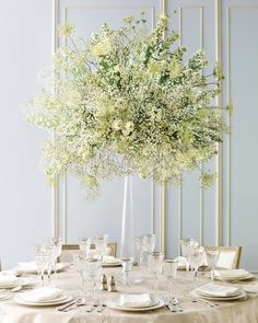 Miniature daisies, doily-shaped Queen Anne's lace, and baby's breath come together in a beautiful balancing act atop a tall, graceful candlestick.
