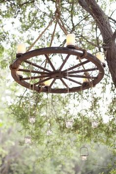 Make your own chandelier with a wooden wheel and candles, looks unique and keeps your country garden theme.