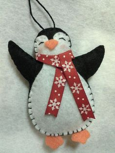 This item is a handmade felt penguin Christmas ornament. It is designed and handmade by me! I make him with either a red, blue or striped