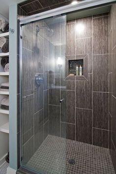 Shower surrounded by 3 walls with glass door opening towards BR door