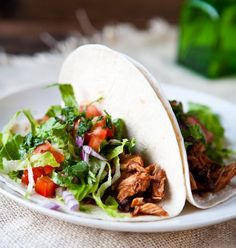 Shredded Chicken Tacos... kind of looks like Chipotle a little :) I'm sure you could cook the chicken in a crock pot and get some super tender chicken :)