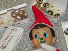 Elf on the Shelf surrounded by donuts boxes, sprinkles and crumbs..Free Elf on the Shelf Printables
