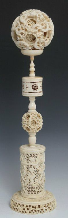 """Large Chinese carved ivory puzzle ball with stand. Ball; Approx. 13 layers with serpentine dragon motif. Stand; Matching dragon motif with thee major elements including an inflated pierced cylindrical base, smaller immobile puzzle ball, and pierced spinning cylinder. Overall height, ~19""""h. Size: 14.875"""" stand, 4"""" ball Weight: 324.6g stand, 240g ball"""