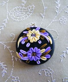 This pendant is handcrafted by me from polymer clay. The base is black and on top I composed purple and skin tone flowers, leaves and petals with