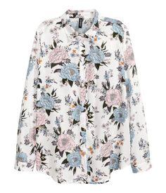 Blanco floral. Camisa en viscosa suave. Modelo de corte recto con un bolsillo superior, botones delante y bajo redondeado.