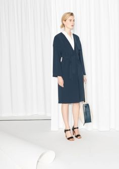 A chic trench coat featuring a soft collar, a tieable waistband to accentuate the waistline, and three concealed snap buttons for closure.