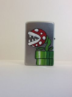 Hand Painted Zippo -- Super Mario Brothers, Venus Fire Trap, Piranha Plant. $30.00, via Etsy.