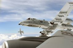 Two A-10 Thunderbolt II aircraft of the 107th Fighter Squadron from Selfridge Michigan, roll away from a KC-135 Stratotanker of the 171st Air Refueling Squadron also from Selfridge Michigan, after an air refueling while flying over Latvia, during the...